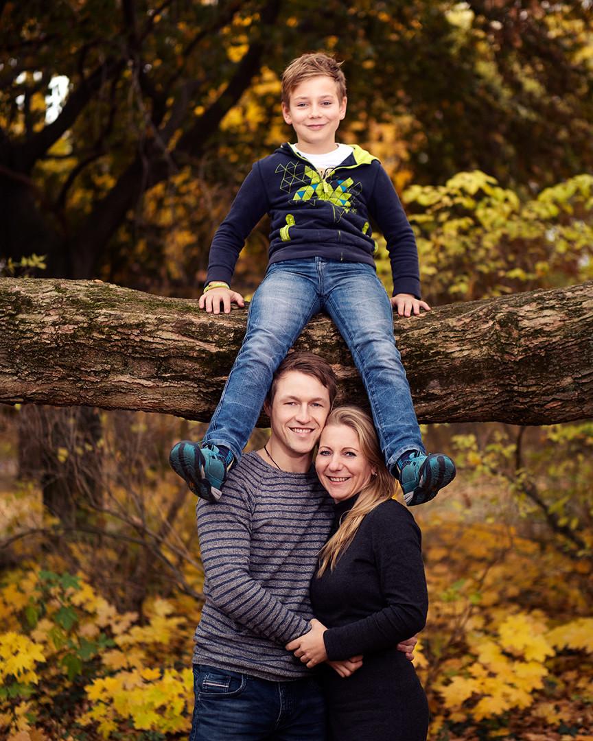 familienshooting leipzig familienfotos fotograf Kind sitzt auf Baum, Eltern darunter