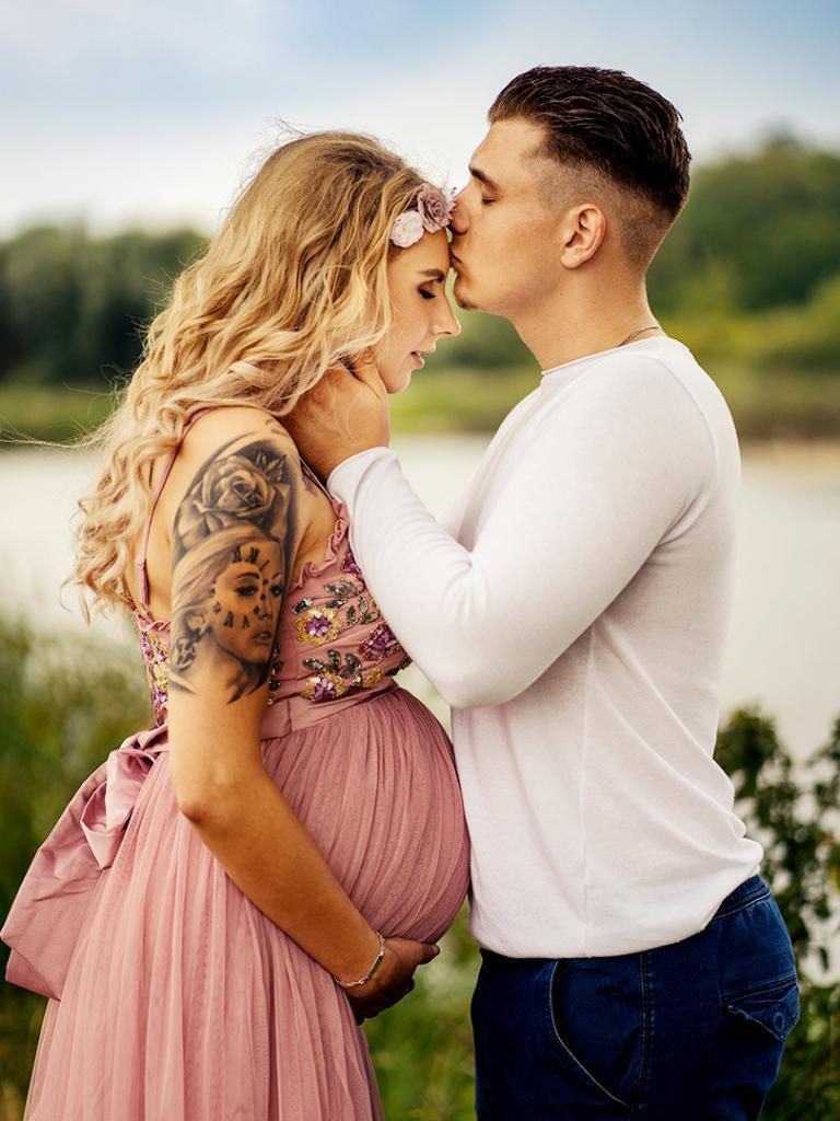 schwangerschaft shooting fotograf leipzig Alexandra mit Babybauch und Lorenz küssen sich