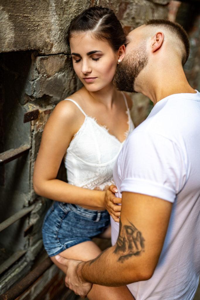 Paarshooting Leipzig Fotograf - Frau sitzt auf dem Geländer, Mann hält sie fest und küsst sie.