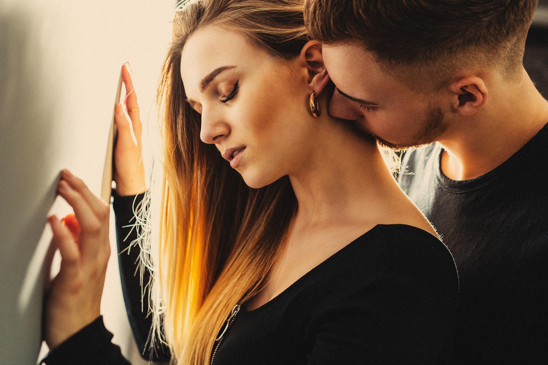 Paarshooting Leipzig Sinnlichkeit Fotograf - Sie lehnt sich an einer Wand an. Er küsst sie sinnlich auf den Hals.