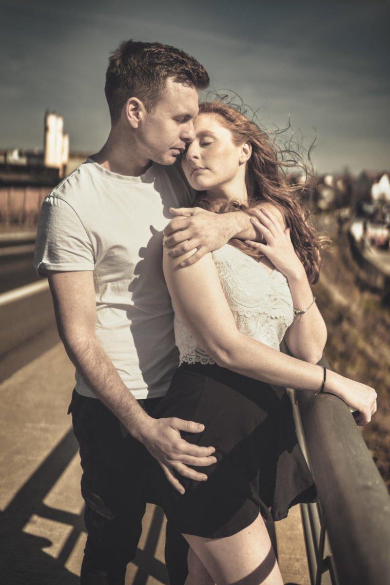 Paarshooting Leipzig Fotograf - Paar steht am Geländer an der Straße. Er hält sie liebevoll von hinten umfasst.