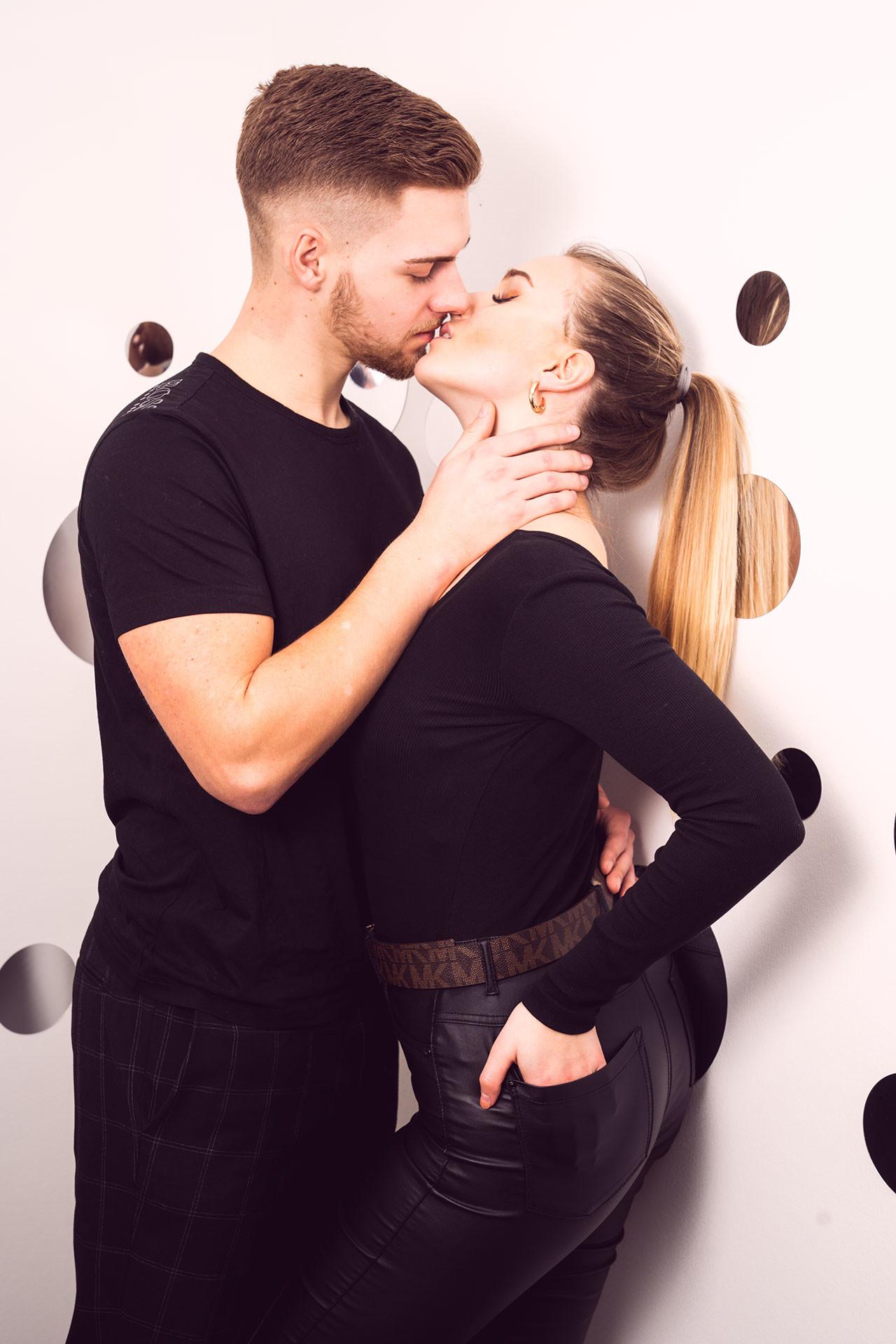 Paarshooting Leipzig - Annabel hat die Hände in den Gesäßtaschen. Tim hält ihren Hals sanft fest und will sie küssen.