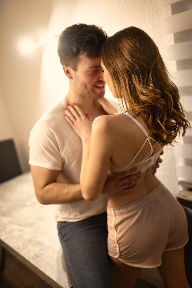 Paarshooting Leipzig -Tobias sitzt auf dem Küchentisch und zieht Mandy an sich heran, welche vor ihm steht.