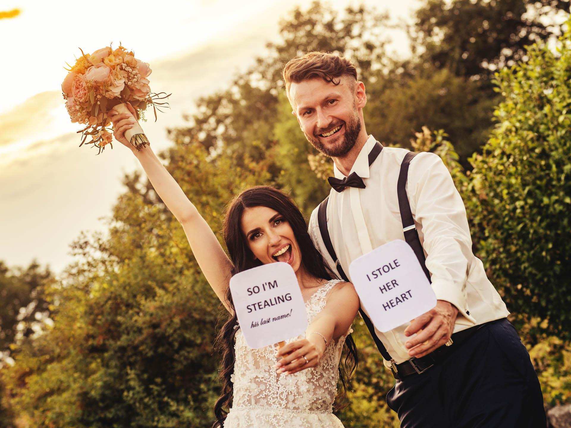 """Hochzeitspaar hält lachend zwei Schilder hoch: """"I stole her heart"""", """"So I´m stealing his last name"""""""